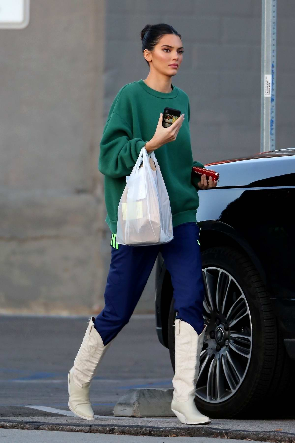 Kendall Jenner sports a green sweatshirt, blue track pants with knee high boots as she arrives for a photoshoot at Milk Studio in Los Angeles