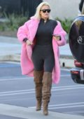 Khloe Kardashian rocks pink fur coat with dark blue jumpsuit and knee high suede boots while stopping by at Kanye's office in Calabasas, California