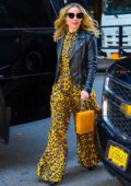 Kristen Bell wears a yellow and black animal print jumpsuit with a leather jacket while out in New York City