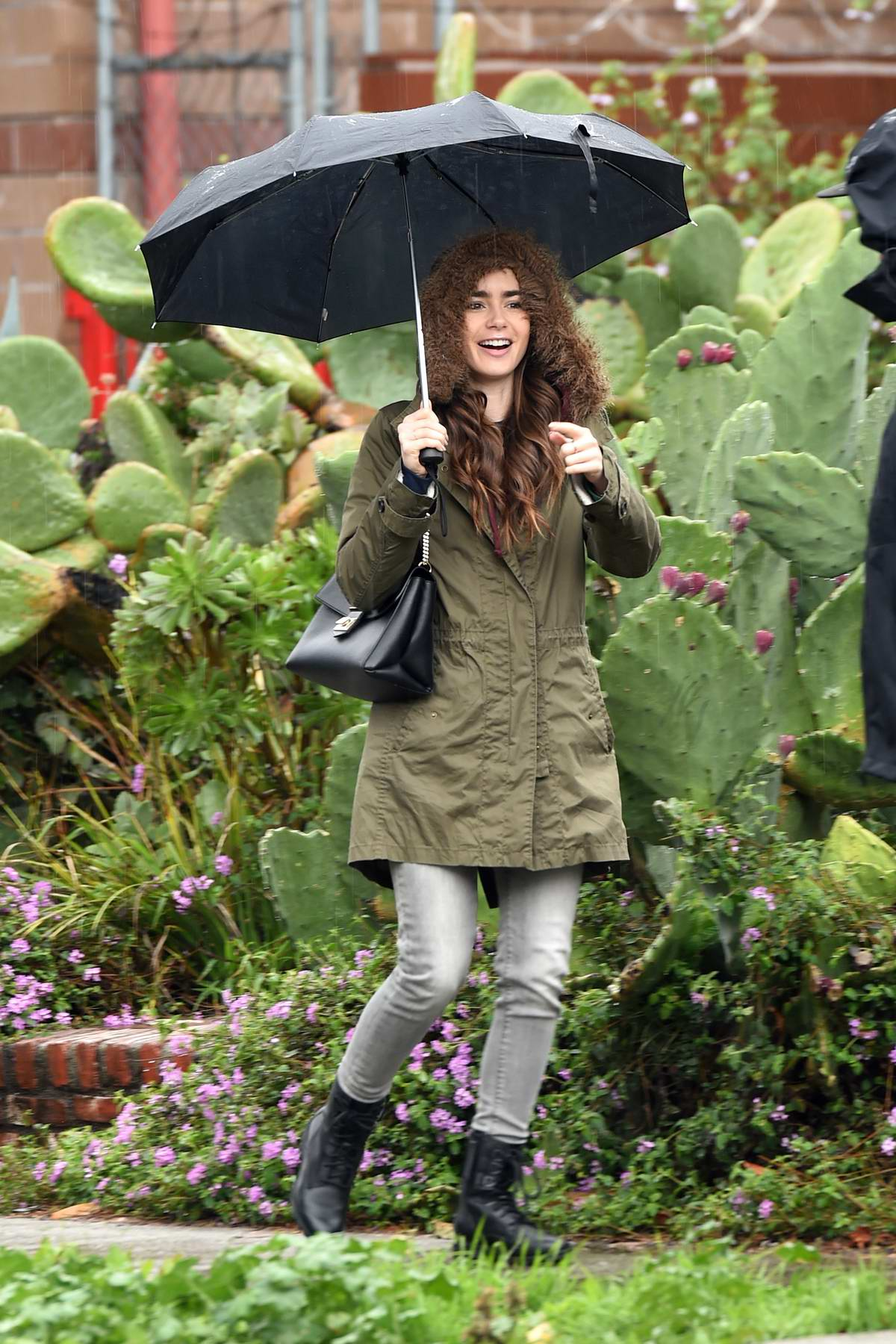 Lily Collins is all smiles as she steps out in the rain while leaving a holistic studio in Los Angeles