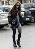 Lily Collins keeps warm on a cold and rainy day with a Starbucks coffee run in Los Angeles