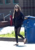 Lily Collins seen wearing a black bomber jacket, partially sheer leggings and sandals as she leaves the gym in Los Angeles