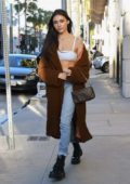Madison Beer rocks a white bra top and jeans with brown long coat while out shopping on Rodeo Drive in Beverly Hills, Los Angeles