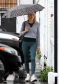 Margot Robbie wears a cropped grey jacket and green leggings as she arrives at the gym holding an umbrella in Los Angeles