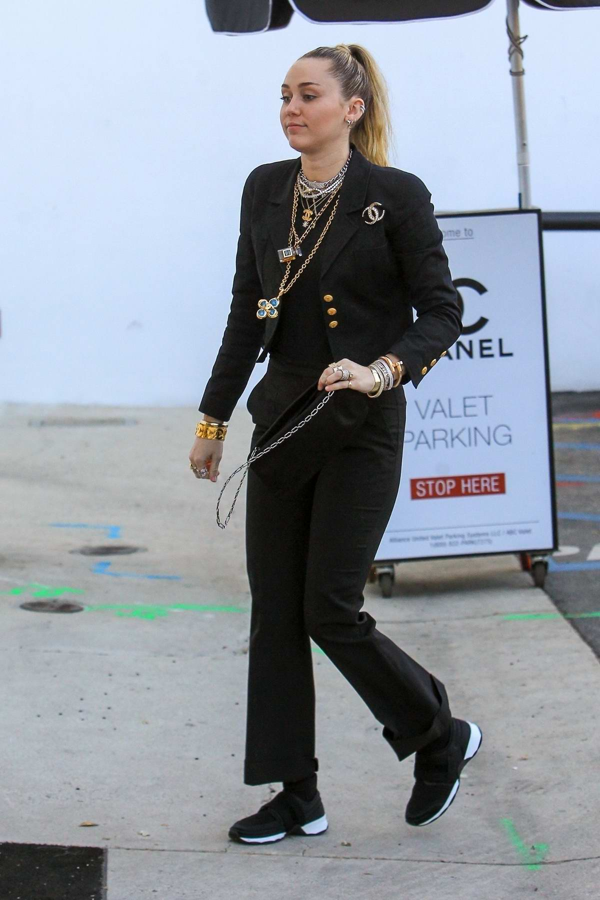 Miley Cyrus wears a Chanel suit and poses with a fan before heading into a Chanel Store in Beverly Hills, Los Angeles
