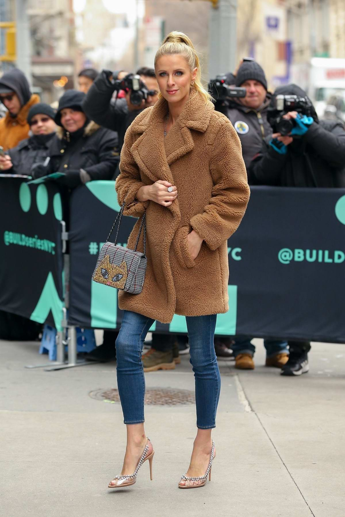 Nicky Hilton arrives at AOL Build Series wearing a brown jacket and blue skinny jeans in New York City