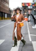 Olivia Culpo shows off her fall winter style in a brown leather coat, white dress, green boots with a hat while out during NYFW in New York City