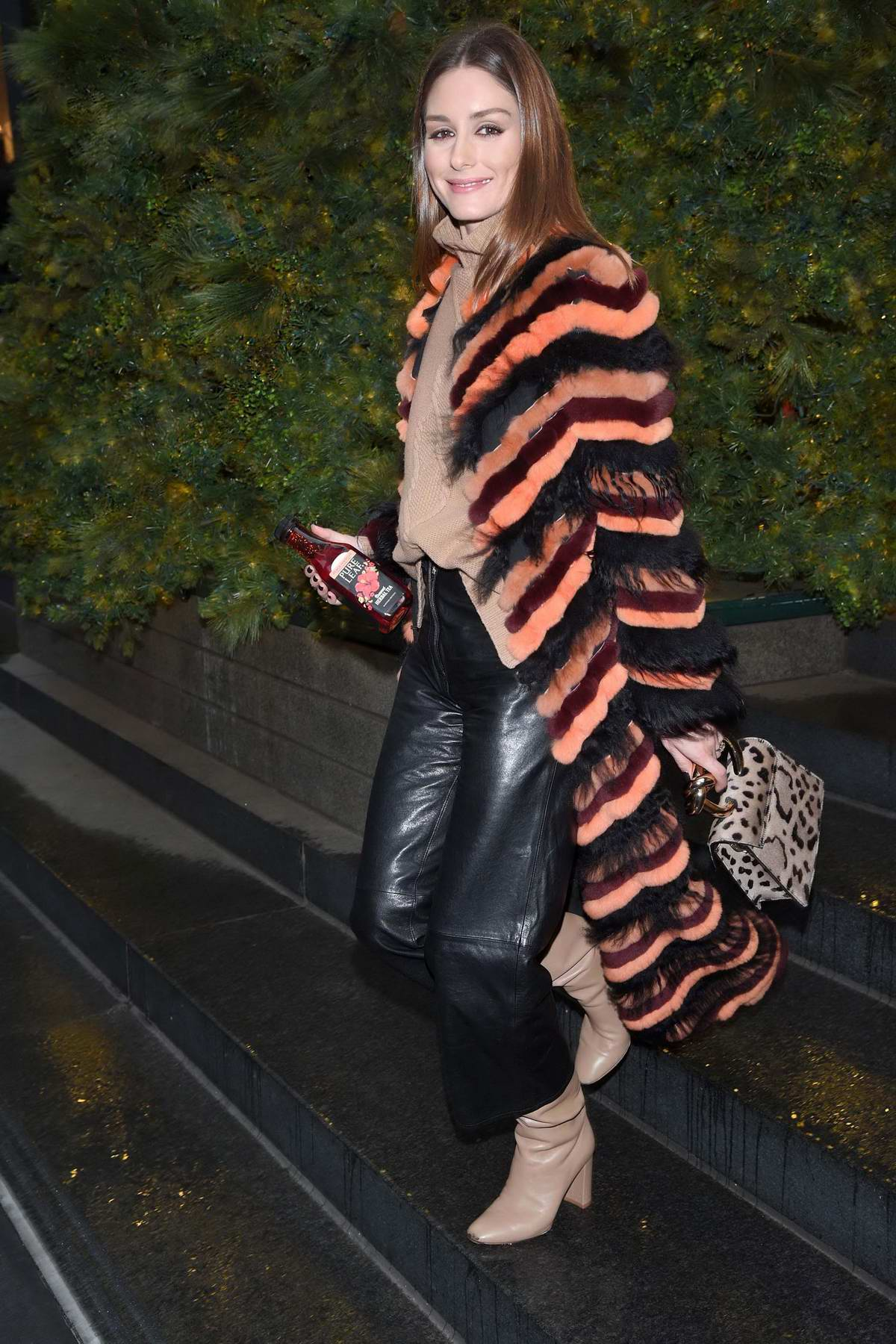 Olivia Palermo look chic in an orange and black fur coat, black leather pants and beige sweater with matching boots while out in New York City