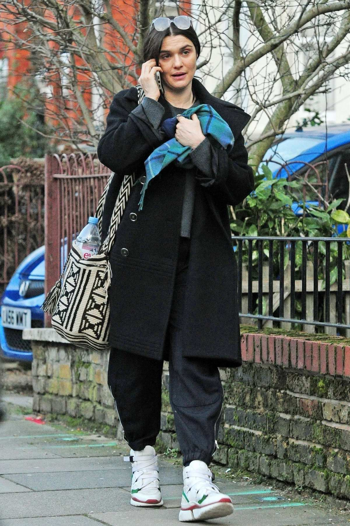 Rachel Weisz keeps warm in a black long coat and trainers as she steps out in London, UK