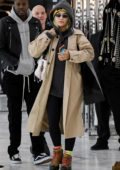 Rita Ora bundles up in a beige trench coat and colorful beanie while shopping at Saint Laurent on Rodeo Drive in Beverly Hills, Los Angeles