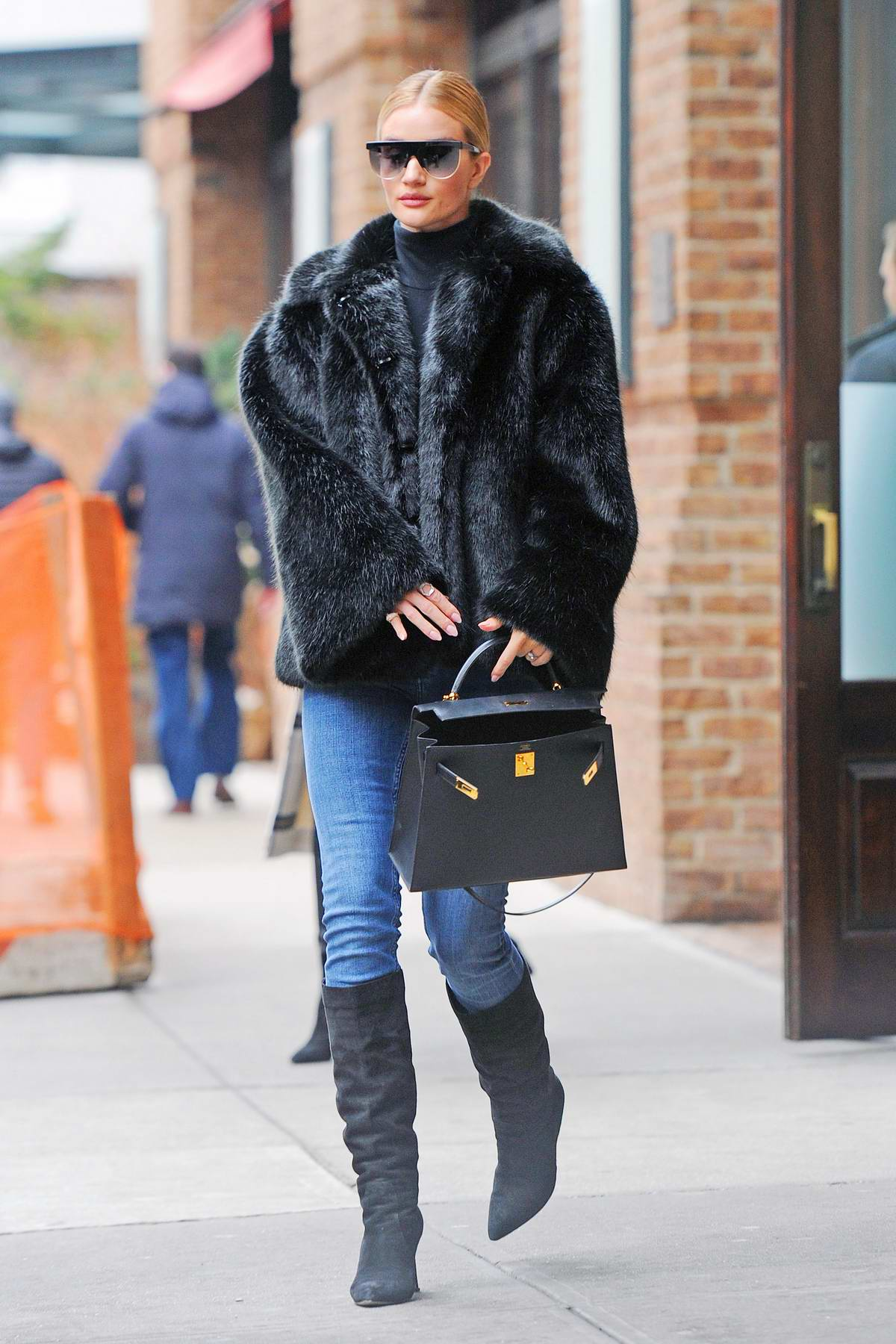 Rosie Huntington-Whiteley looks chic in a black fur coat, blue jeans and knee high black suede boots as she leaves The Greenwich Hotel in New York City