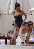 Selena Gomez wears a dark green swimsuit while lounging with her friends by the beach in Cabo San Lucas, Mexico