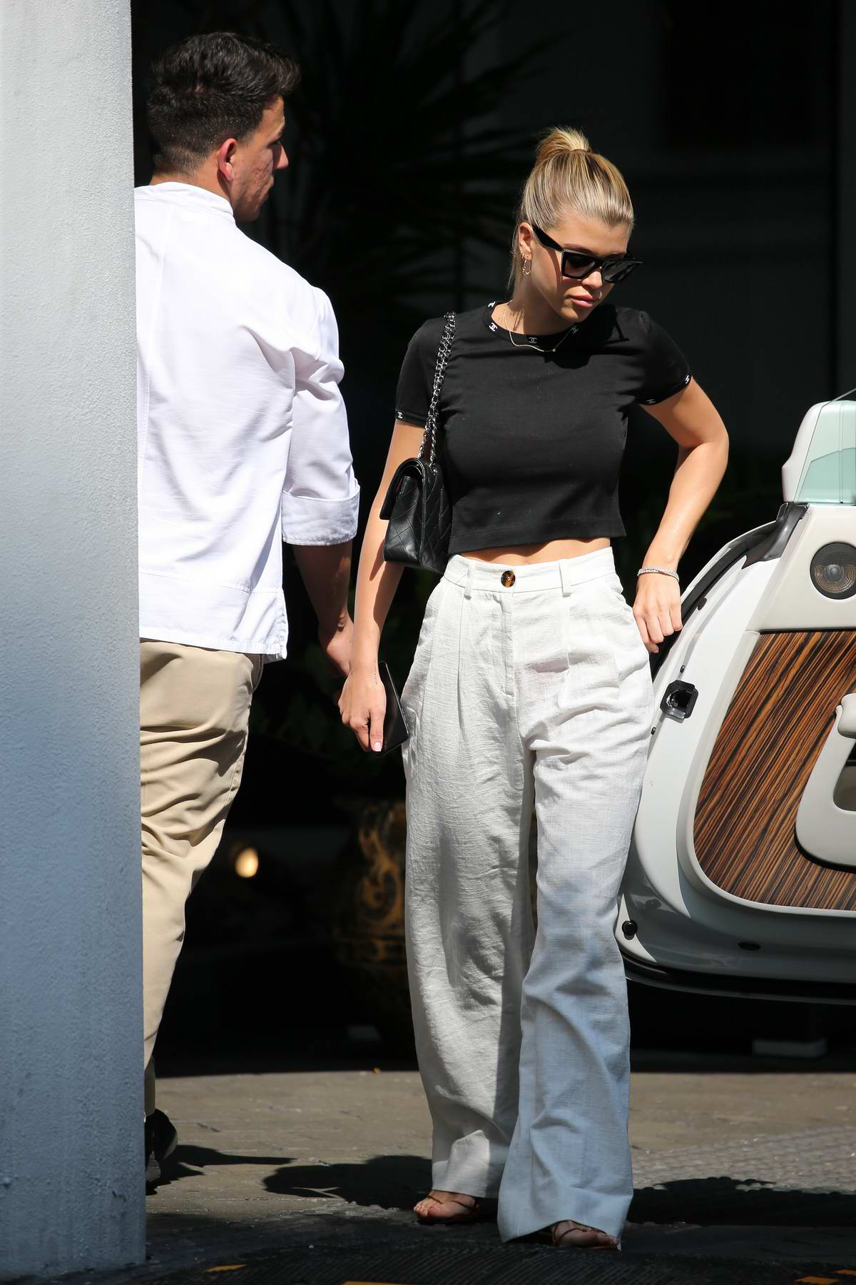 Sofia Richie keeps it casual in a black top and white trousers while out in Miami, Florida