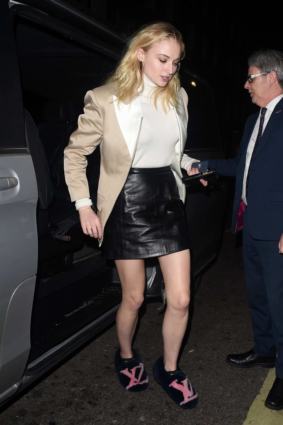 Sophie Turner spotted in a beige blazer, black leather mini-skirt and Louis Vuitton slippers as she leaves Corinthia Hotel in London, UK