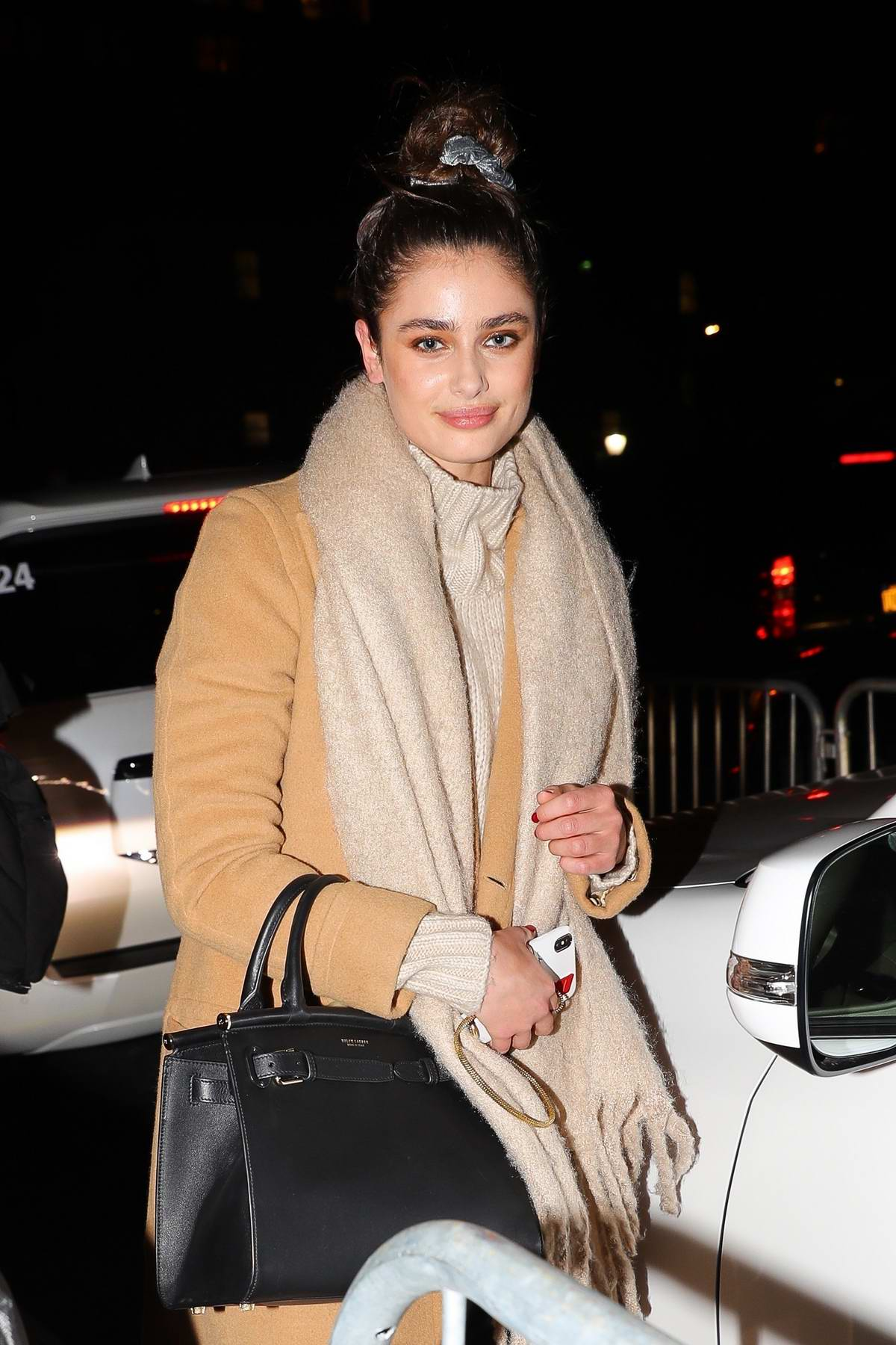 Taylor Hill bundles up in a beige coat, scarf and leather pants for the Prabal Gurung Fashion Show during NYFW in New York City