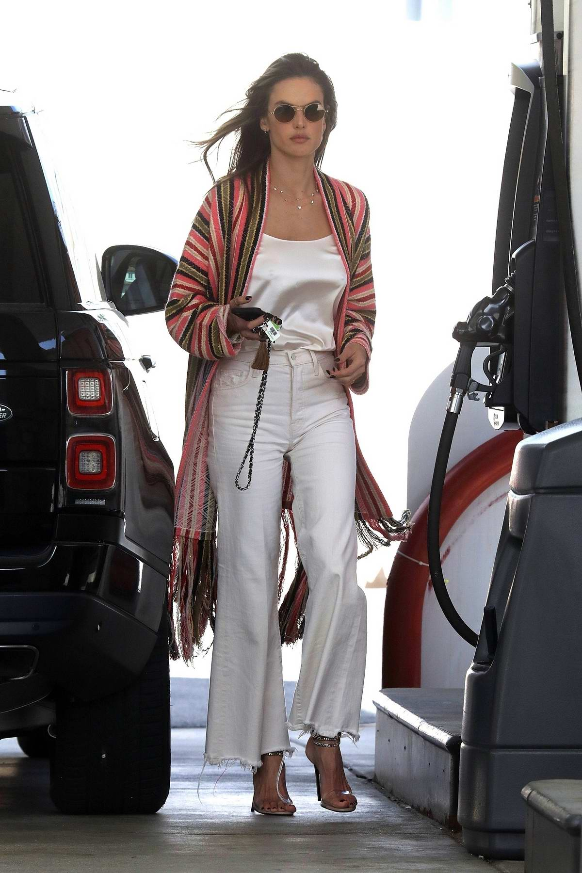 Alessandra Ambrosio looks stunning in a colorful duster over a white tee and flare jeans as she fuels up her Range Rover in Malibu, California