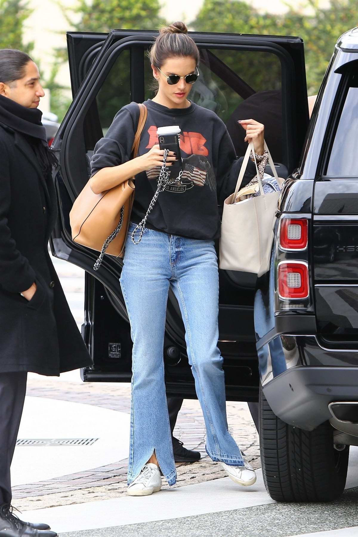Alessandra Ambrosio keeps it trendy with a sweatshirt, jeans and white Golden Goose sneakers while arriving for a meeting in Beverly Hills, Los Angeles