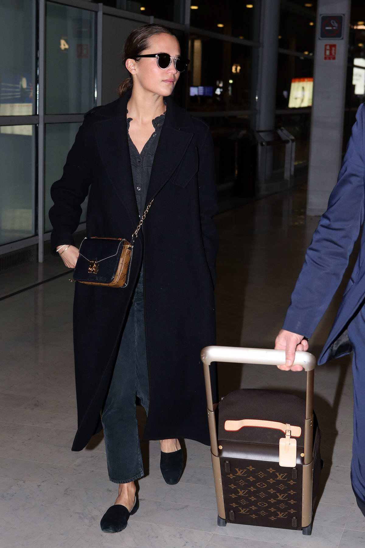 Alicia Vikander seen wearing a denim jumpsuit with black long coat as she arrives CDG airport in Paris, France