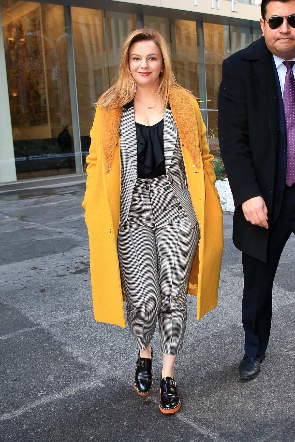 Amber Tamblyn steps out in a mustard yellow coat with with a grey suit during a promotional tour in New York City