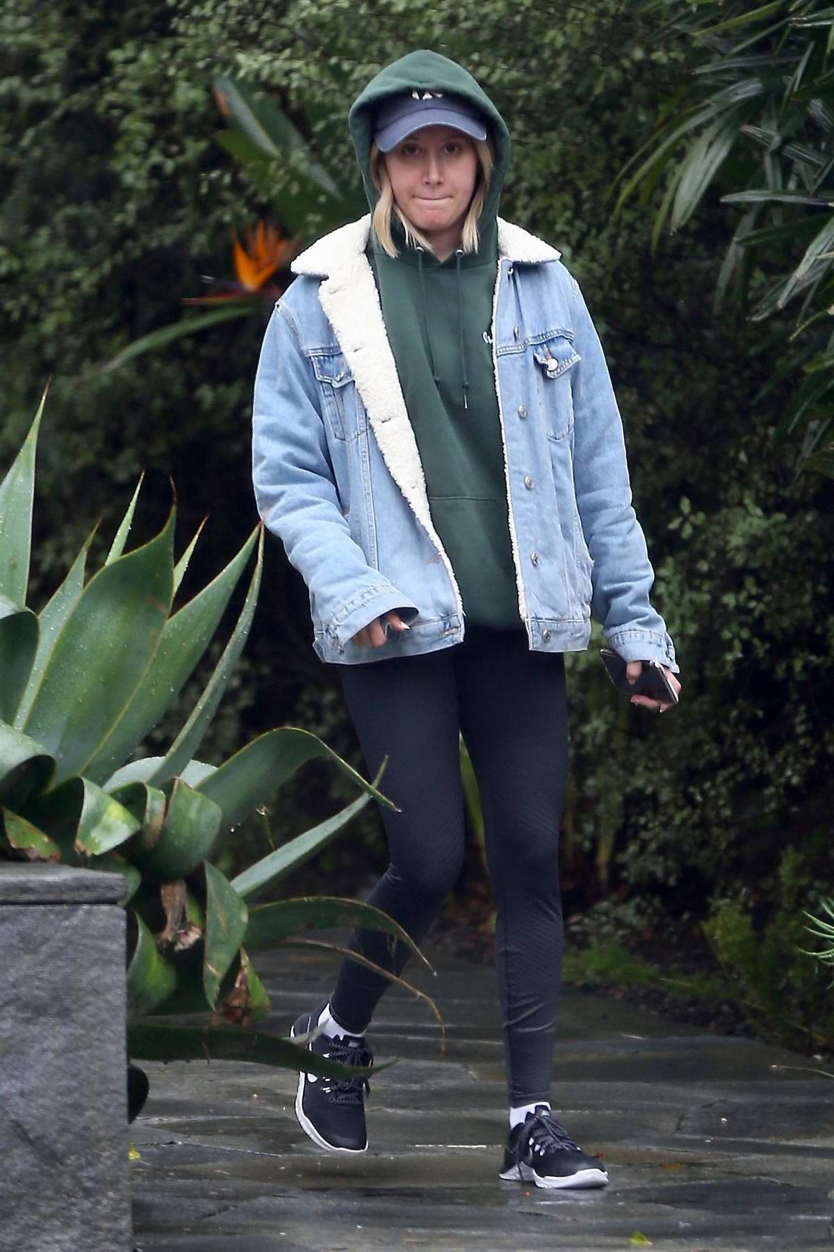 Ashley Tisdale wears a denim jacket with a green hoodie and leggings while out shopping on a rainy day in West Hollywood, Los Angeles
