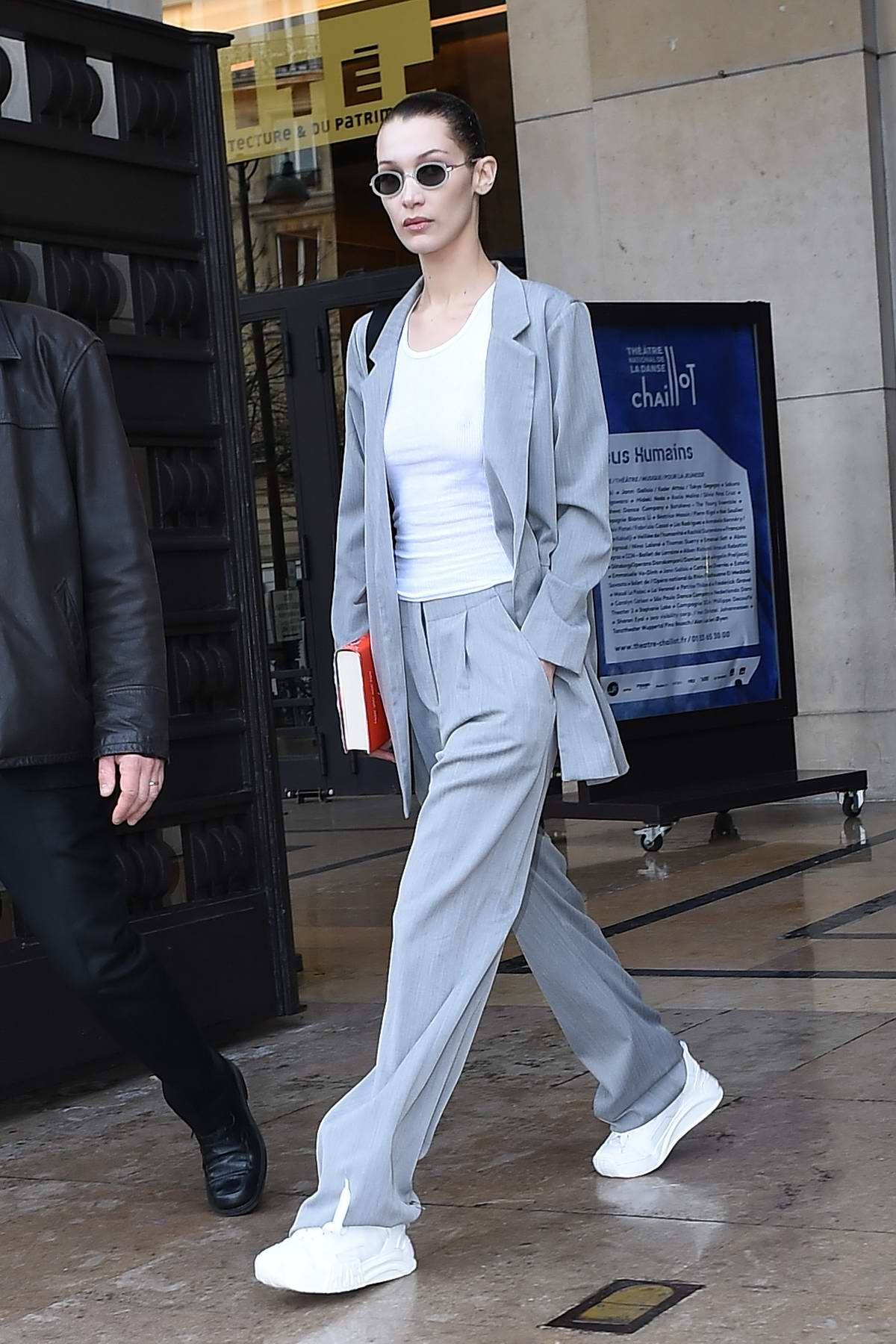 Bella Hadid sports a gelled hair look with a grey suit as she leaves Ackermann Fashion Show during Paris Fashion Week in Paris, France