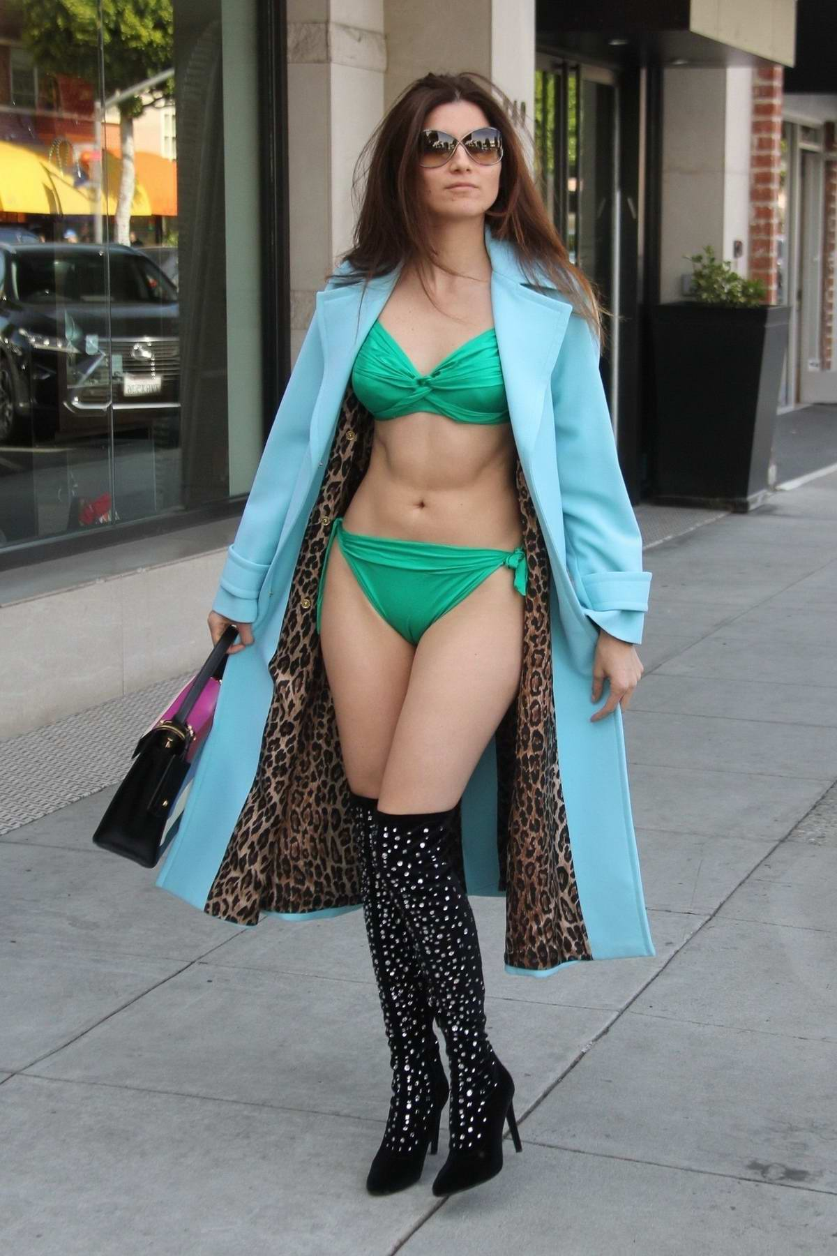 Blanca Blanco wears a blue trench coat over a green bikini while out shopping for swimsuits in Beverly Hills, Los Angeles