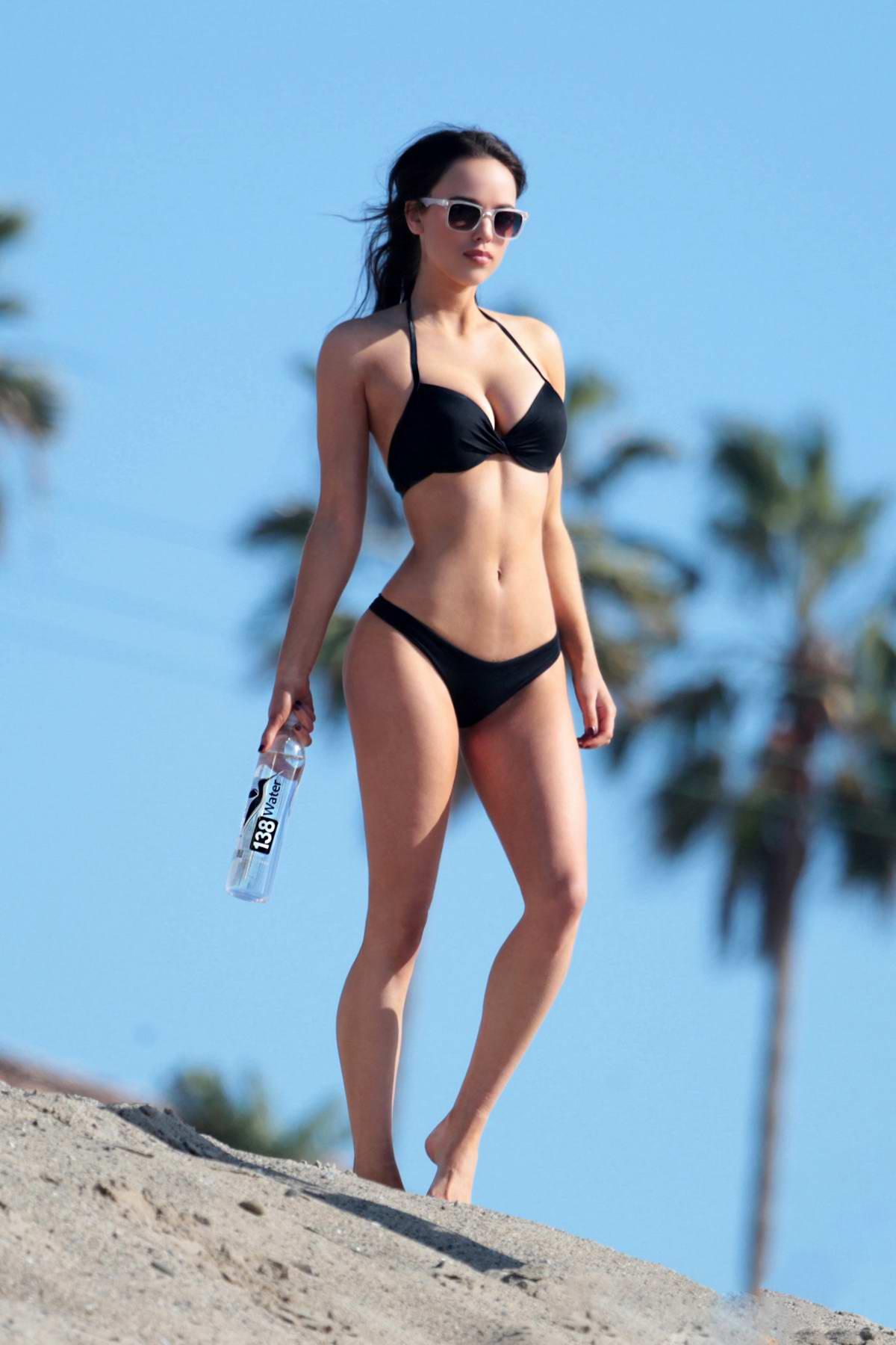 Cate Chant poses in a black bikini during a beach photoshoot for 138 Water in Malibu, California