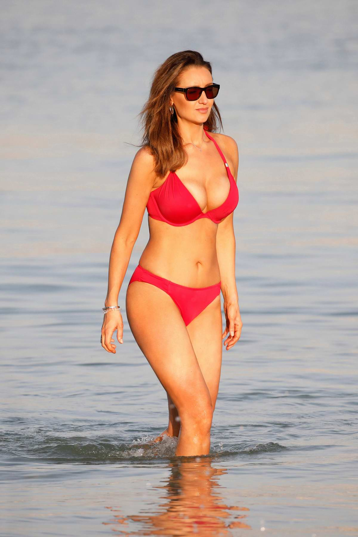 Catherine Tyldesley stuns in a red bikini while on the beach at Le Royal Meridien Hotel in Dubai, UAE