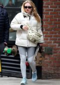 Dakota Fanning bundles up in a white parka and grey leggings while out shopping in New York City
