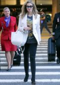Delta Goodrem looks sharp in a white blazer and black pants as she touches down at LAX in Los Angeles