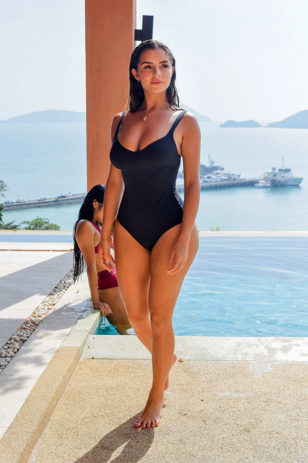 Demi Rose wears a black swimsuit while relaxing by the pool in Phuket, Thailand