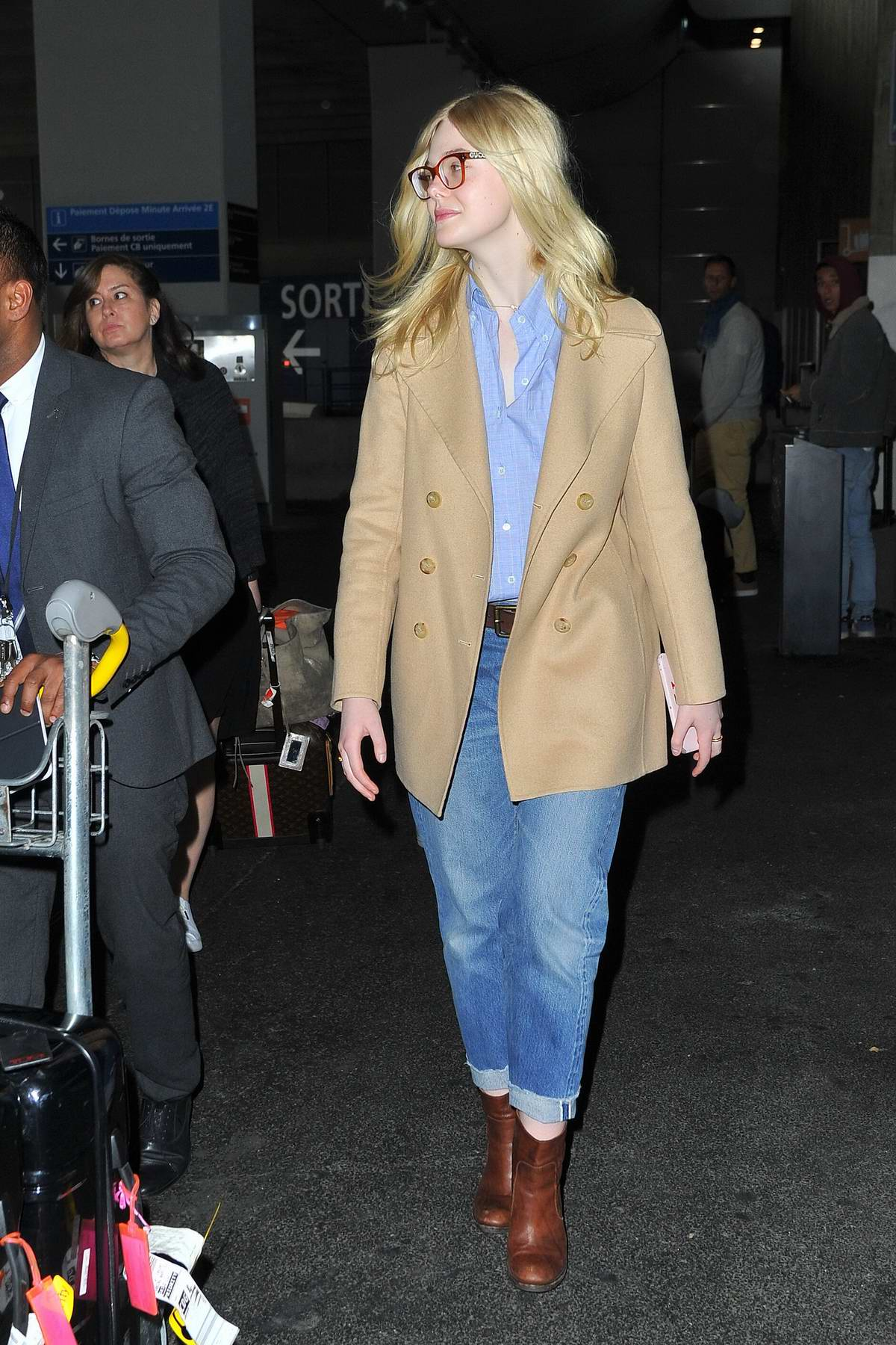 b709e3f0195211 elle fanning sports gucci glasses paired with a tan blazer, blue shirt,  jeans and brown boots as she arrives at the cdg airport in paris,  france-030319_10