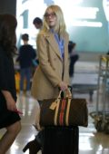 Elle Fanning sports Gucci glasses paired with a tan blazer, blue shirt, jeans and brown boots as she arrives at the CDG Airport in Paris, France