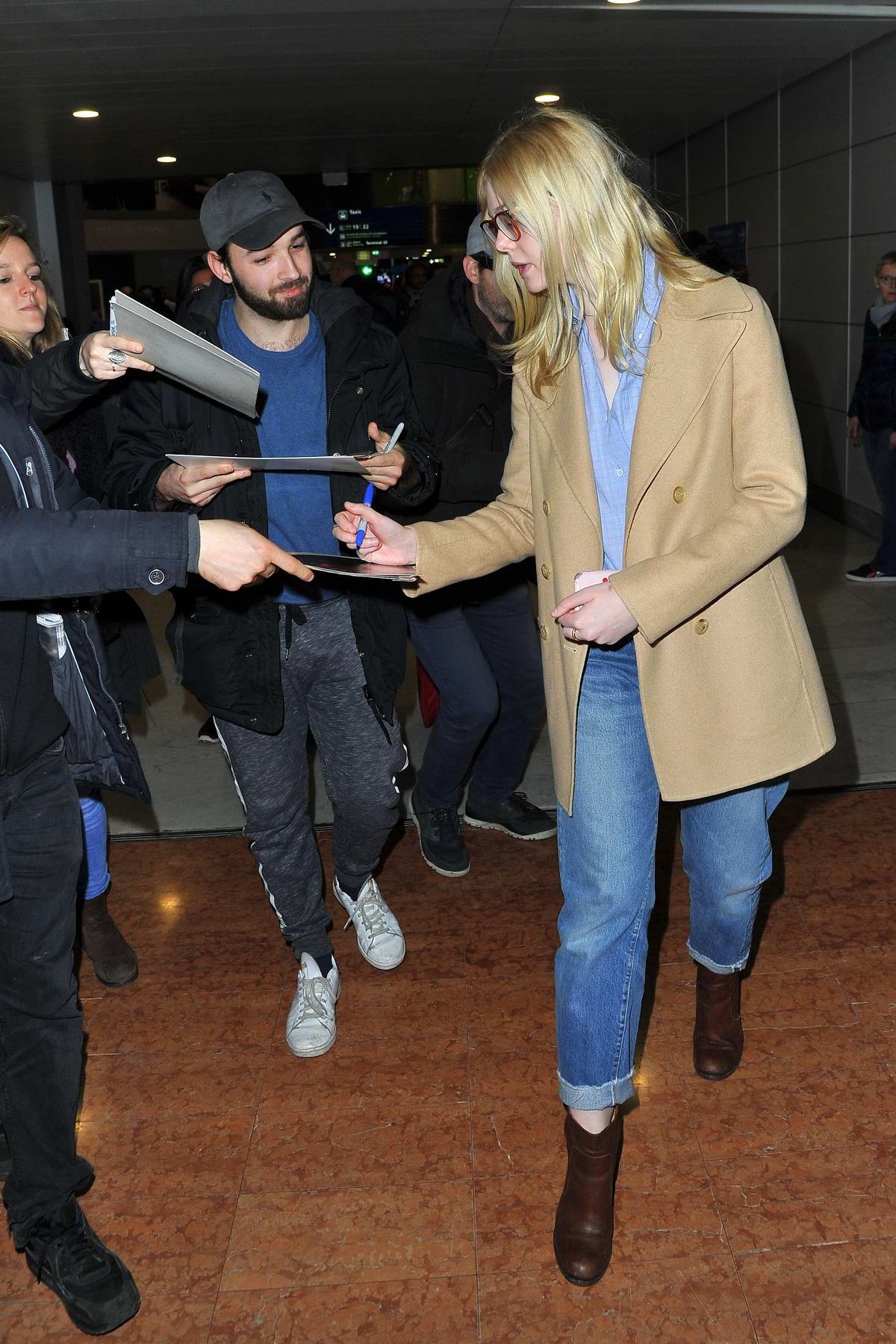 8c1f5332451a6b elle fanning sports gucci glasses paired with a tan blazer, blue shirt,  jeans and brown boots as she arrives at the cdg airport in paris,  france-030319_8