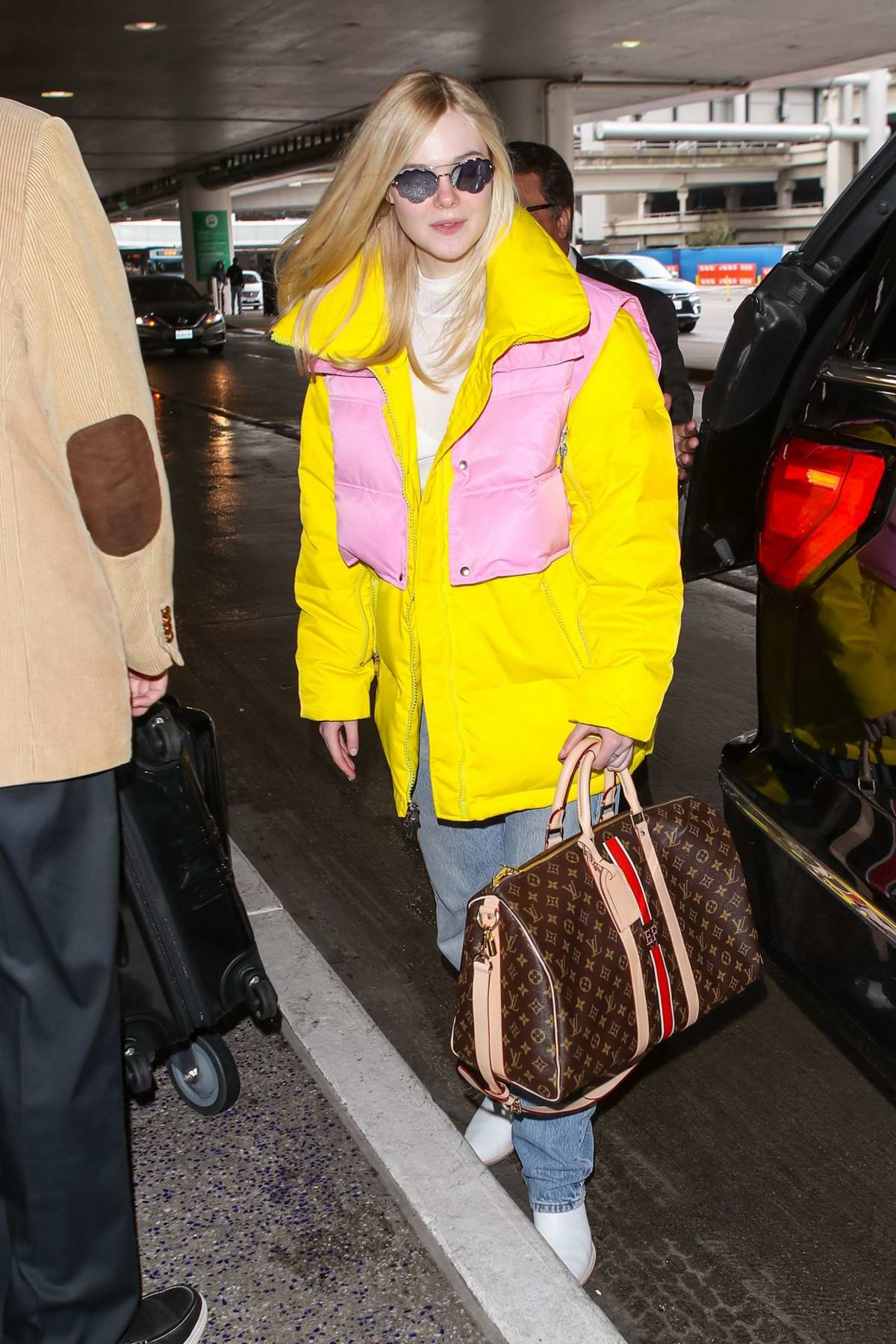Elle Fanning stands out in a bright yellow and pink puffer jacket as she lands at LAX Airport in Los Angeles