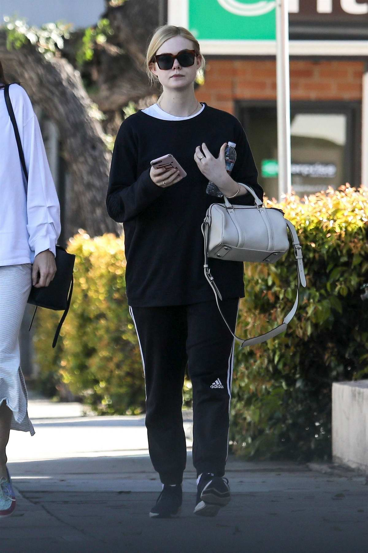 Elle Fanning steps out in black Adidas sweats during a trip to a nail salon with her mother in Los Angeles