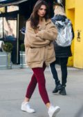 Emily Ratajkowski keeps warm in a beige Sherpa jacket and red leggings while out on a stroll in New York City