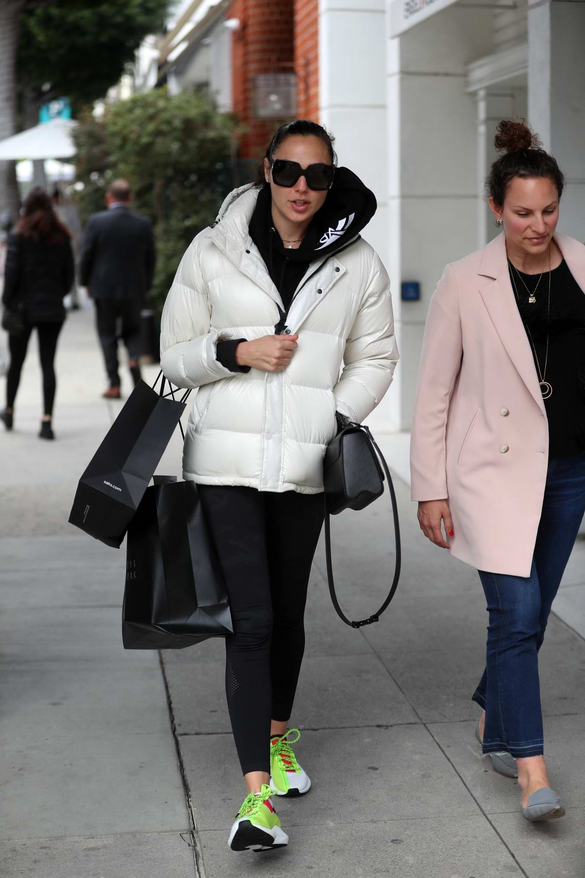 Gal Gadot wears a white puffer jacket and black leggings while out shopping at Saks and Barneys New York in Beverly Hills, Los Angeles