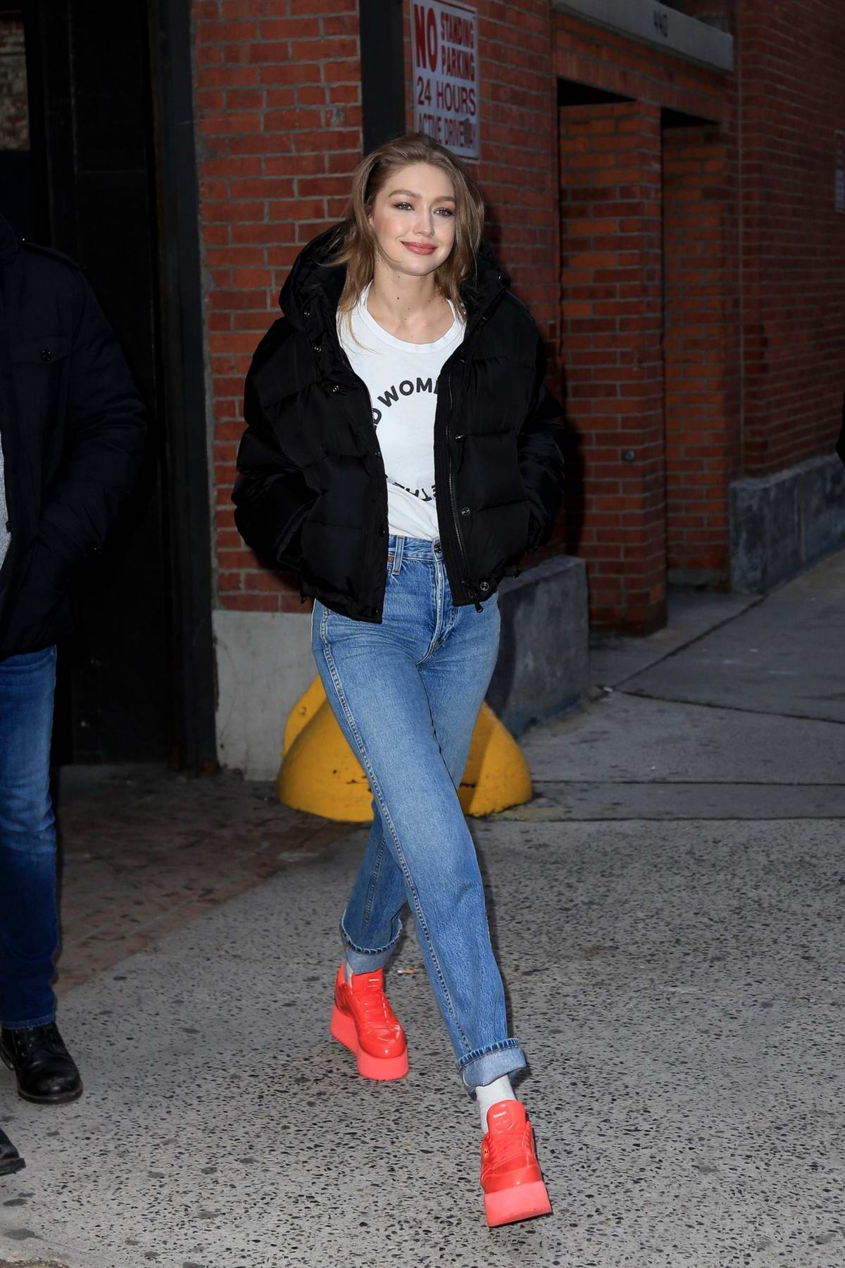 Gigi Hadid keeps it trendy with a parka, white tee, jeans and red sneakers as she leaves a studio after a Maybelline photoshoot in New York City