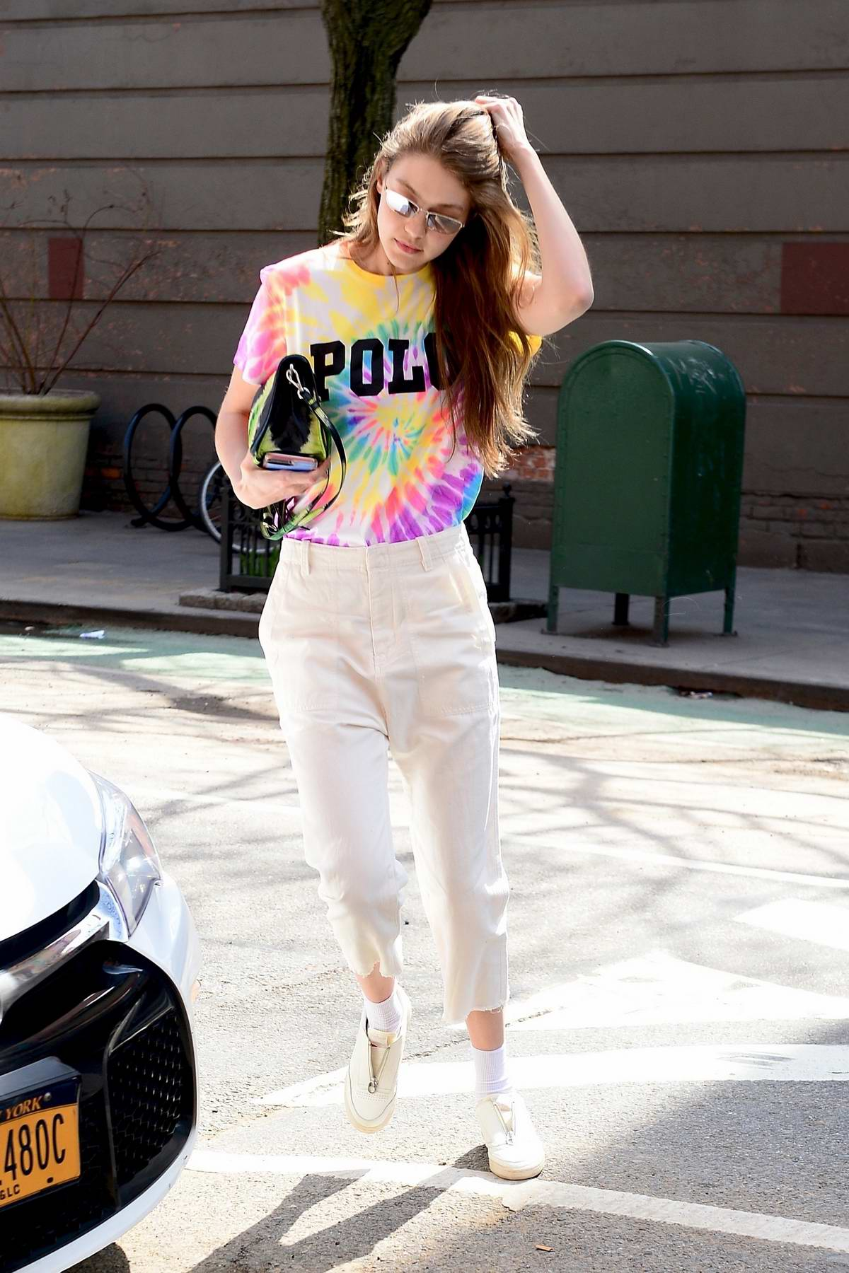 Gigi Hadid steps out rocking a tie dye shirt with white capri pants in New York City