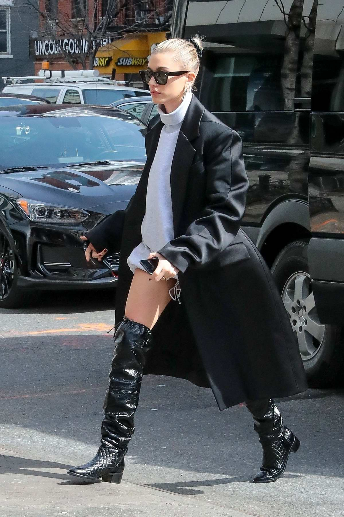 Hailey Baldwin Bieber looks chic in a turtleneck mini dress paired with a black long coat and thigh high black boots while out in New York City