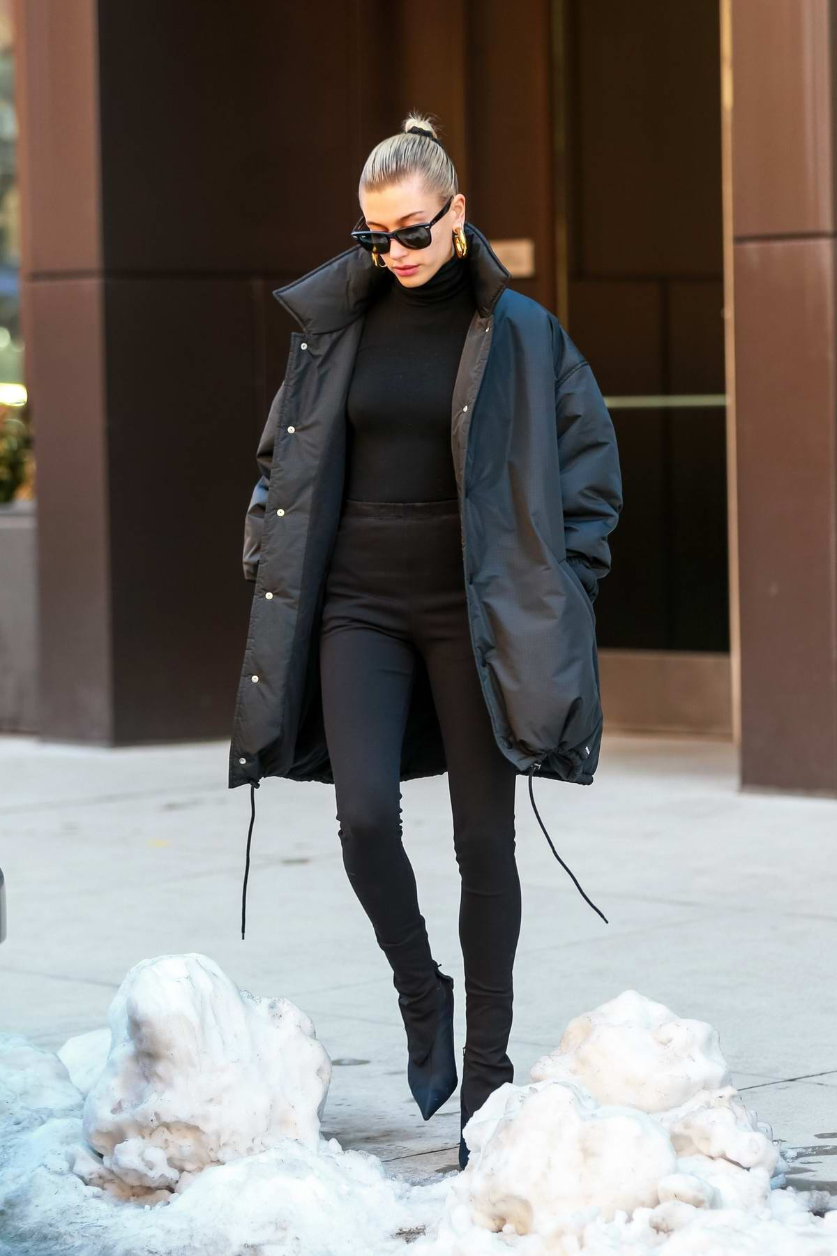Hailey Baldwin Bieber looks chic in all black as she makes her way around piles of snow to get to her ride in New York City