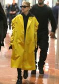 Hailey Baldwin Bieber stands out in a bright yellow long coat as she arrives on an early flight at the CDG aiport in Paris, France