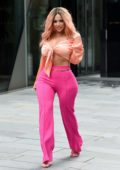 Holly Hagan stands out in bright pink pants and knotted peach top as she arrives at LullaBellz photoshoot in Manchester, UK