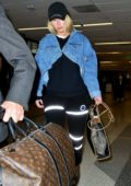 Iggy Azalea rocks a stylish denim jacket with a black ensemble as she arrives at LAX Airport in Los Angeles