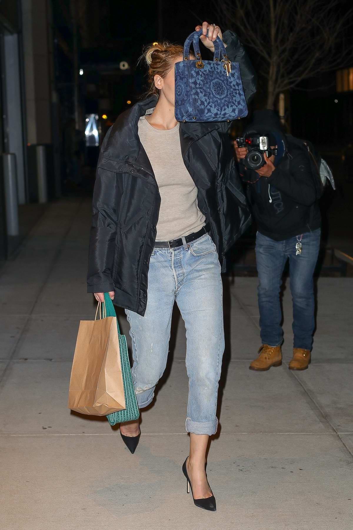Jennifer Lawrence cover her face with her purse as she leaves a restaurant in New York City