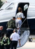 Jennifer Lopez shows off her perfect waistline in a cropped grey hoodie and sweatpants while boarding a private jet in Miami, Florida