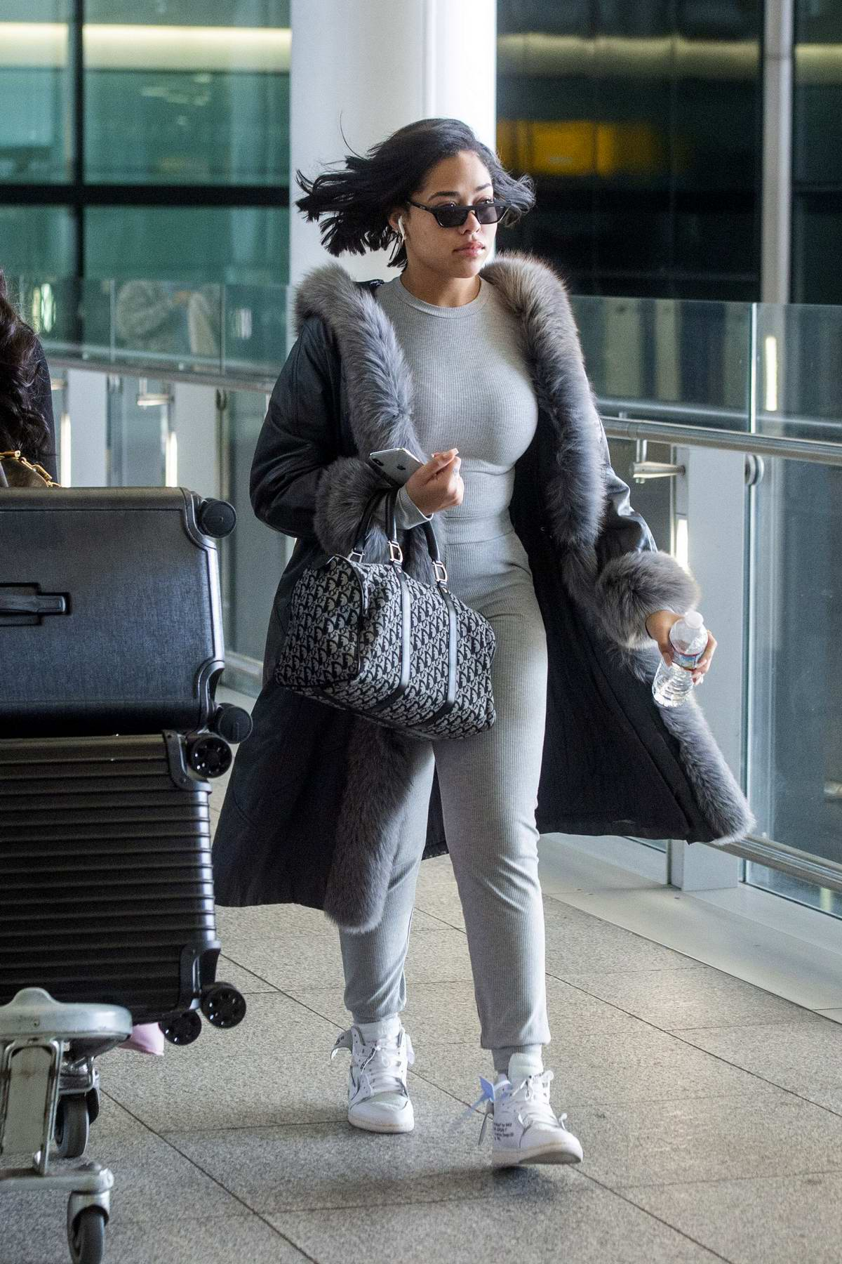 Jordyn Woods dressed in fur trimmed coat and grey sweatsuit as she arrives at Heathrow Airport in London, UK