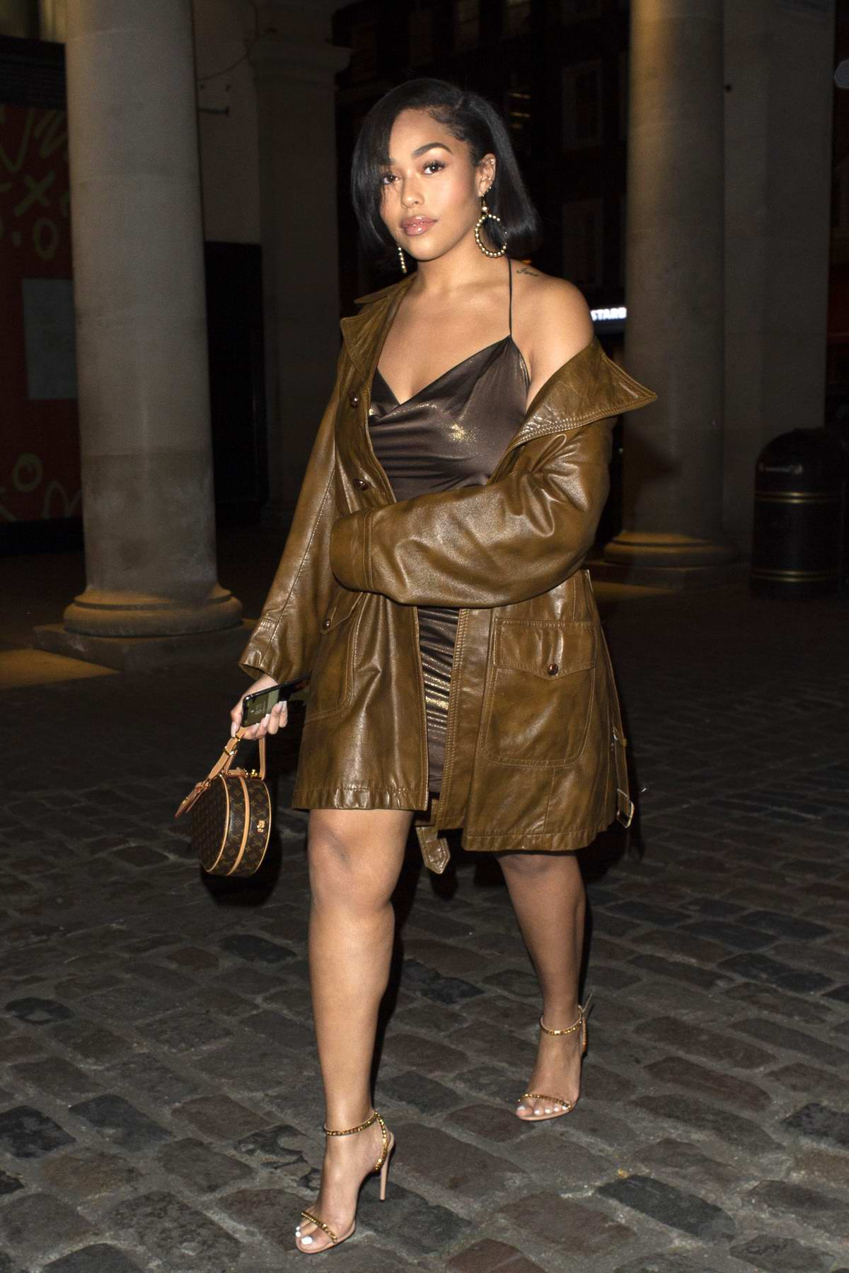 Jordyn Woods wears a brown mini dress with matching leather jacket while out for dinner with her mother at Sushisamba in London, UK