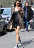 Kaia Gerber rocks a short black dress with a tweed coat while out sipping on an iced coffee on a sunny day in New York City